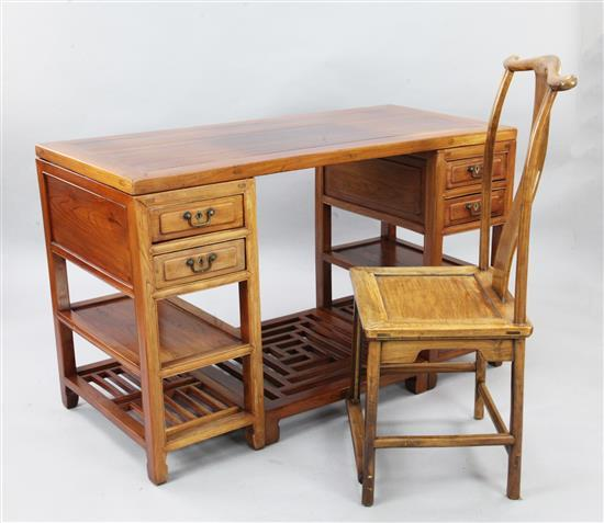 A Chinese elm wood pedestal desk and a hardwood yoke back chair, late 19th century, width 135 cm, height 83cm