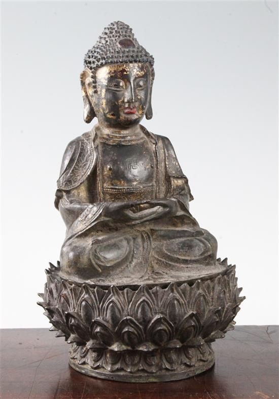 A Chinese lacquered bronze seated figure of Buddha Shakyamuni, Ming dynasty, 16th/17th century, height 28cm