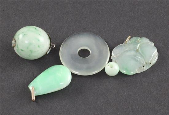 A group of four Chinese jadeite pendants or beads and a similar hardstone disc, late 19th/20th century, largest 3.3cm