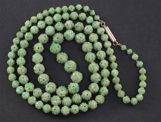 A Chinese carved jadeite bead necklace, early 20th century, total length 72.5cm, largest bead 9mm