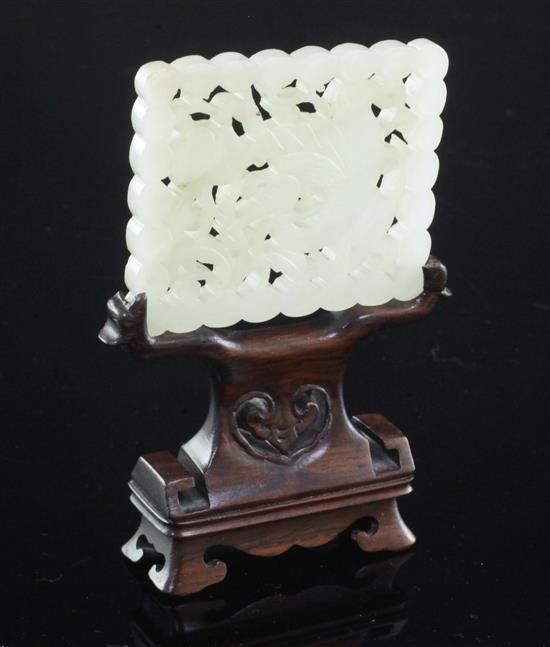 A Chinese pale celadon jade plaque, 18th / 19th century, 6.1cm, wood stand