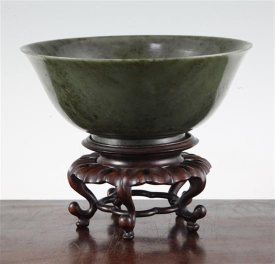 A Chinese spinach green jade bowl, 18th century, diameter 19cm, wood stand