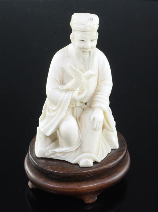 A Chinese ivory seated figure of a scholar holding a bird, early 20th century, wood stand, total height, 10cm