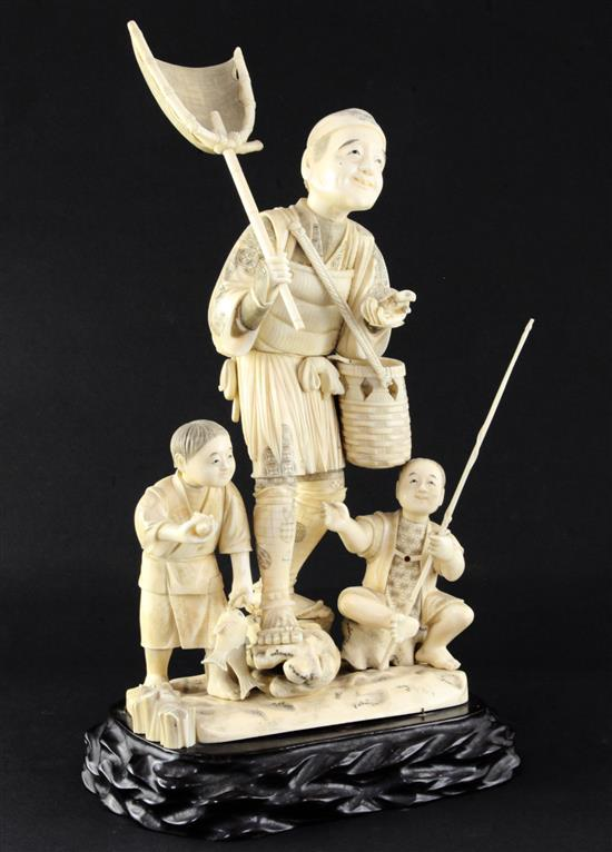 A large Japanese sectional walrus ivory okimono of a fisherman and two boys, early 20th century height including wood stand, 40cm