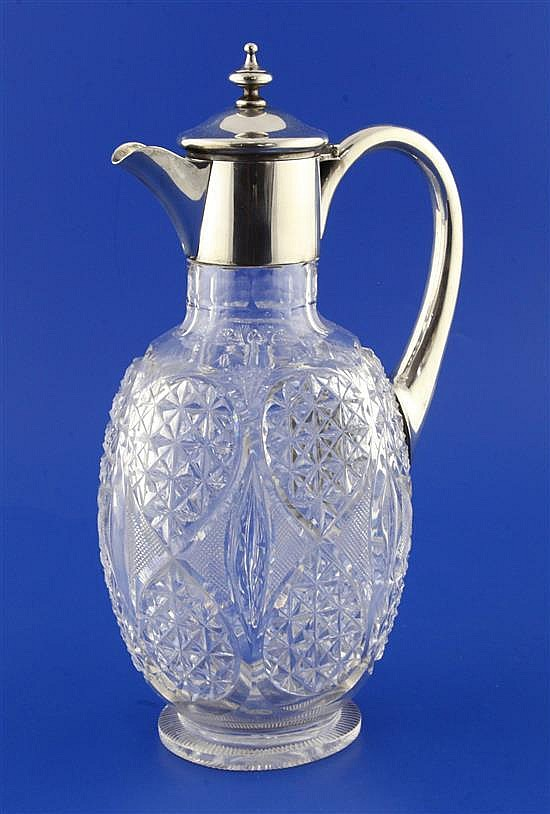 An Edwardian silver mounted cut glass claret jug by William Comyns, 11in.