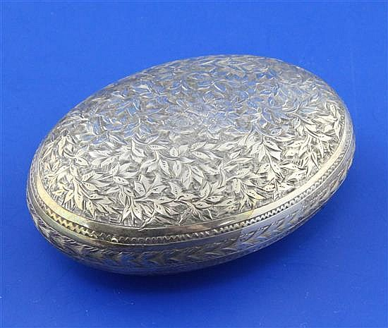 A Victorian chased silver oval tobacco box by George Unite, 2.5 oz.