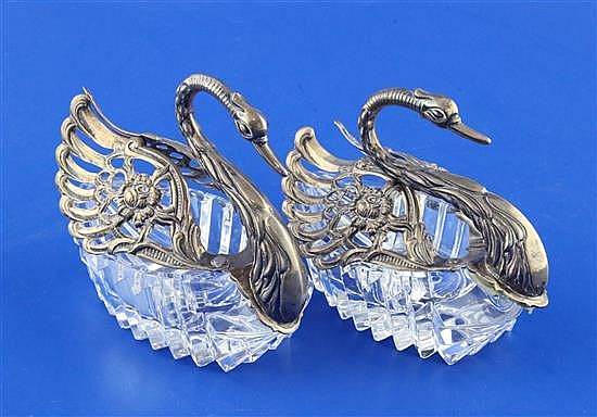 A pair of 1980's repousse silver mounted cut glass sweetmeat dishes modelled as swans, height 4in.
