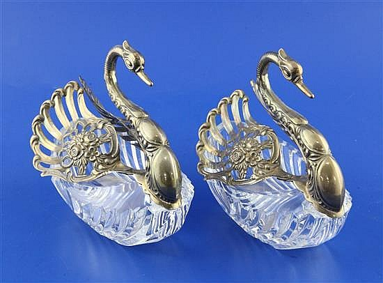 A pair of 1990's repousse silver mounted cut glass sweetmeat dishes modelled as swans, height 6in.