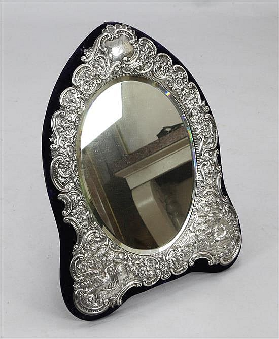 A late Victorian large repousse silver mounted oval dressing table easel mirror by Carrington & Co, 23.5 in overall.