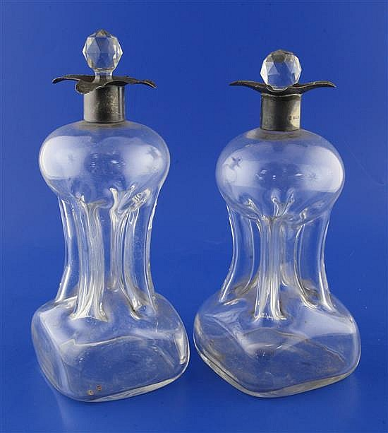 A near pair of Edwardian silver mounted four lipped waisted glass decanters with glass stoppers, 10.5in et infra.