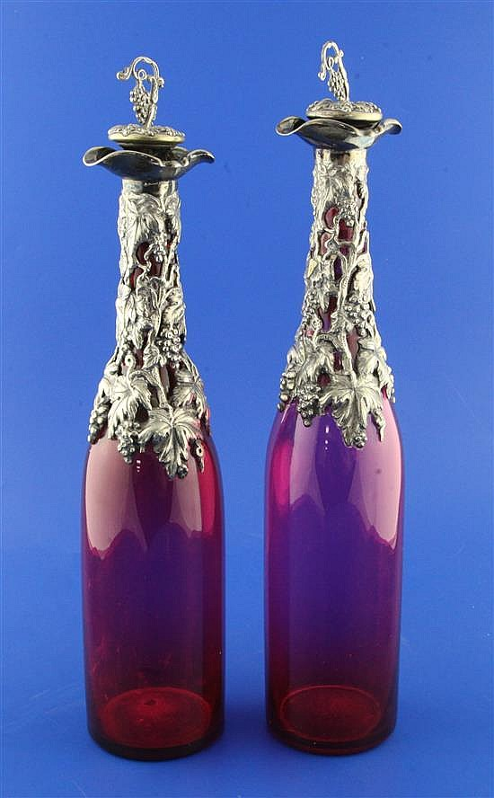 A pair of early 20th century plate mounted double lipped ruby glass bottle decanters & stoppers, 14.25in.
