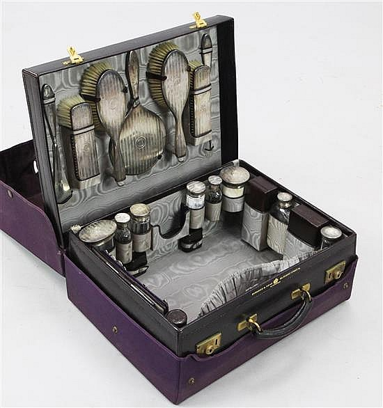 An early 20th century leather travelling toilet case containing twenty engine turned silver mounted jars etc. by Edwards & Sons.