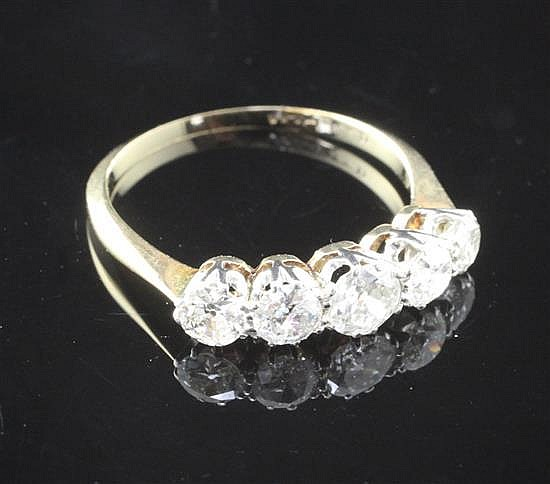 A mid 20th century 18ct gold and platinum five stone graduated diamond ring, size O.