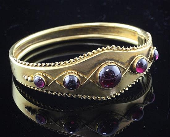 A Victorian gold and graduated cabochon almandine garnet hinged bangle, gross 16 grams.
