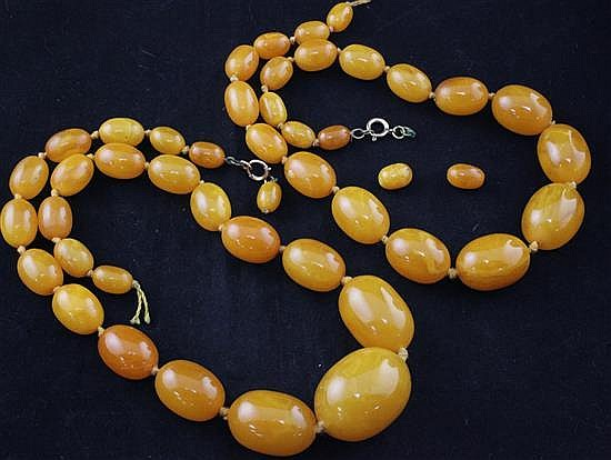 Two single strand graduated oval amber bead necklaces, gross weight 121 grams.