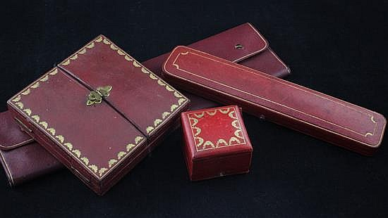Three assorted early 20th century Cartier jewellery boxes and a pouch.