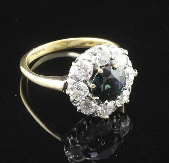 An 18ct gold, sapphire and eight stone diamond cluster ring, size M.