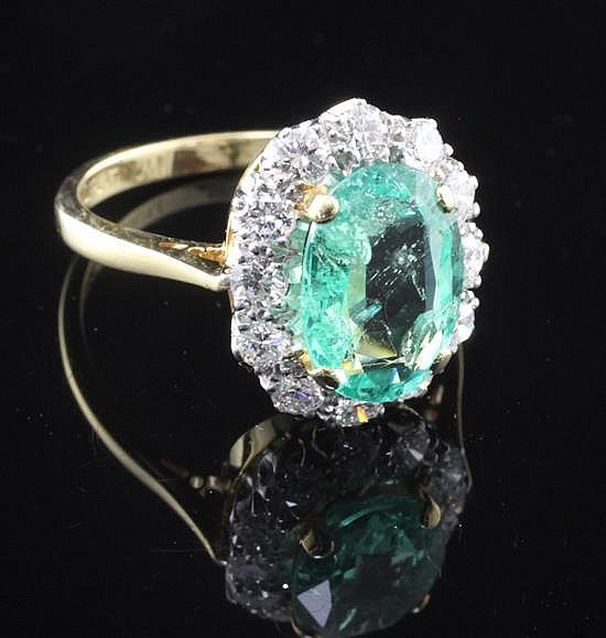 An 18ct gold and platinum, emerald and diamond cluster ring, size O.