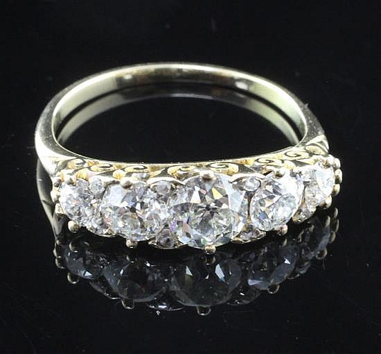 A gold and graduated five stone diamond half hoop ring, size L.