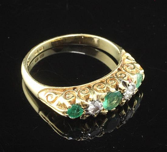 An 18ct gold and graduated five stone emerald and diamond half hoop ring, size K.