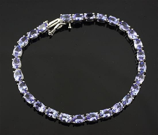 A 14ct white gold and tanzanite line bracelet by Kallati, 7.25in.