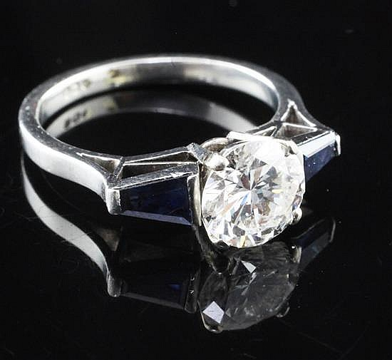 A modern platinum and single stone diamond ring with trapezoid cut sapphire set shoulders, size N.