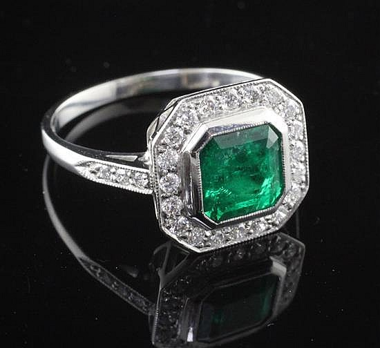 A platinum, emerald and diamond cluster ring, size P.