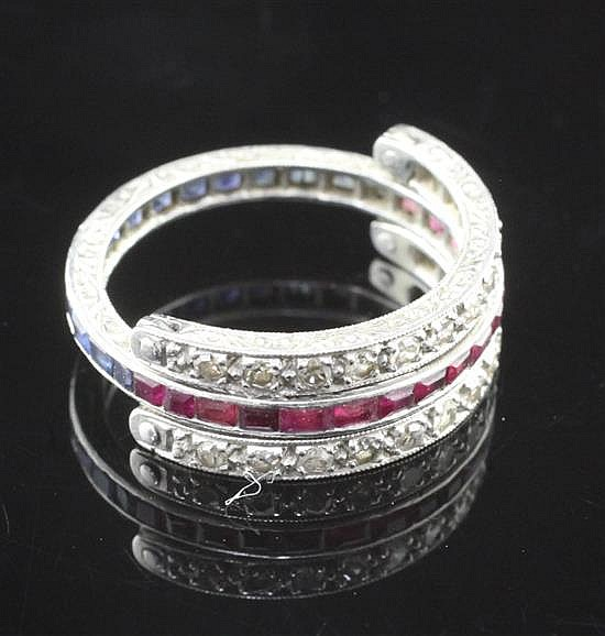 A 1920's platinum, sapphire, ruby and diamond triple eternity ring, size L.