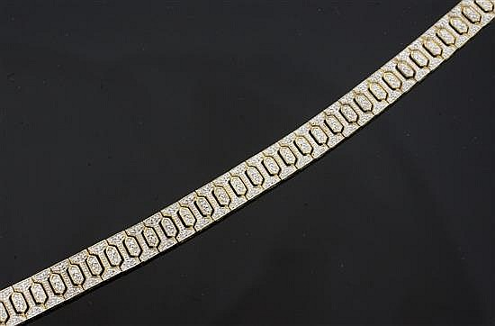 A modern 9ct gold and diamond encrusted bracelet, 7in.