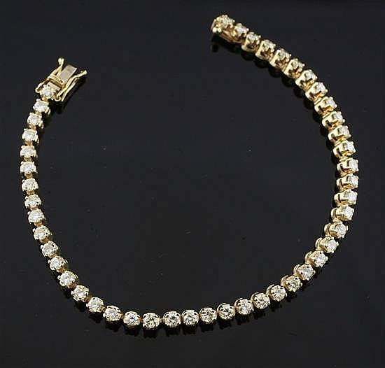 A modern 14ct gold and diamond line bracelet, 7in.