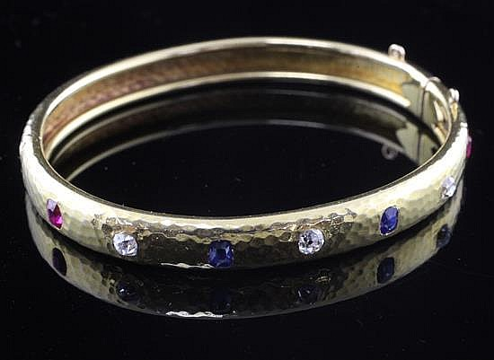 A planished 18ct gold, ruby sapphire and diamond hinged bangle, gross weight 20.4 grams.