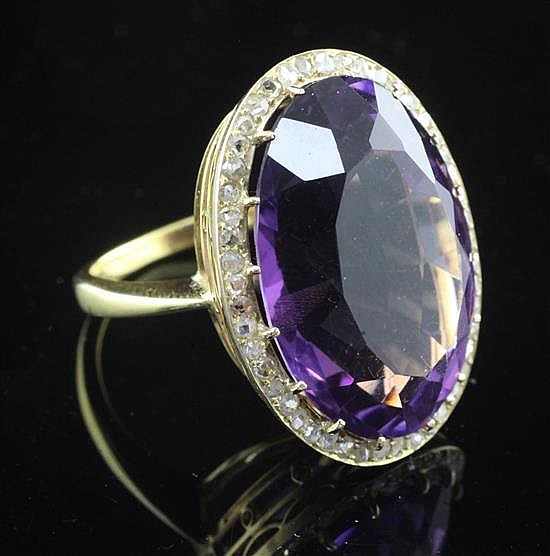 An 18ct gold, amethyst and diamond oval dress ring, size P.