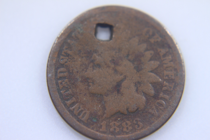 1883 IIndian Head Penny I I have a 1883 Indian Head Penny that has a square hole on top of the penny Please look at picture befor bidding