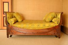 Lit bateau d'époque Restauration en placage d'acajou à décor sculpté de guirlandes de laurier, dossiers renversés, soierie jaune,long. 207 cm