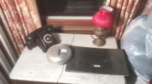 Contents of top of table including vintage telephone, electrified lamp, buck stock certificates book and Bell