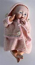 AN EARLY 20TH CENTURY FRENCH BISQUE FIGURE OF A DOLL wearing a pink co