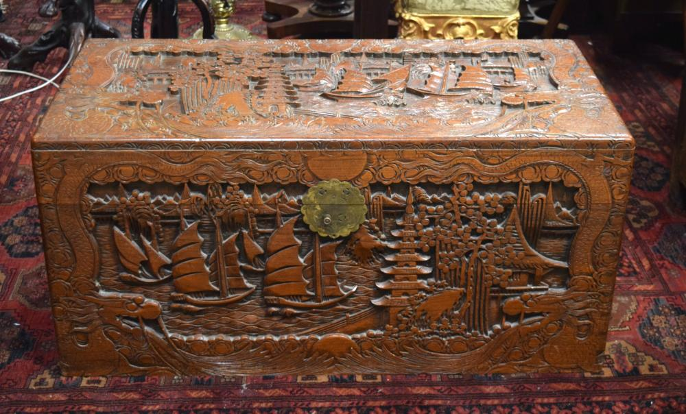 A CHINESE CAMPHOR WOOD LINED CHEST, decorated with boats in a harbour and carved dragons surrounding. 50 x 105 x 52 cm.