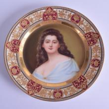 AN EARLY 20TH CENTURY VIENNA PORCELAIN CABINET PLATE painted with a female wearing a blue robe, under a claret and gilt ground. 21 cm diameter.