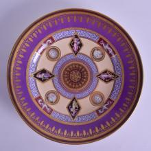 AN 18TH/19TH CENTURY VIENNA PORCELAIN CABINET PLATE painted with unusual black lozenge shaped panels of classical figures, under a purple and gilt ground. 24 cm diameter.