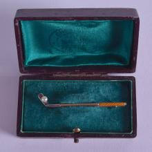 A RARE EDWARDIAN 15CT GOLD AND ENAMEL GOLF CLUB TIE PIN.