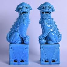 A PAIR OF EARLY 20TH CENTURY CHINESE BLUE GLAZED BUDDHISTIC DOGS OF FOE modelled upon square form bases. 26 cm high.