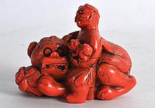 AN UNUSUAL CHINESE QING DYNASTY CARVED FIGURE OF A SCHOLAR AND BUDDHISTIC LION possibly coral, modelled recumbant. 2.75ins wide.