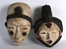 A PAIR OF CARVED AFRICAN MALE AND FEMALE WOODEN MASKS. 11Ins & 10ins long.