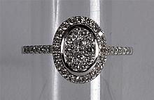 A 9CT GOLD OVAL DIAMOND PAVE SET RING.