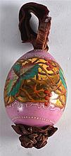 A RUSSIAN PINK PORCELAIN EASTER EGG painted with acorn leaves upon a gilt a
