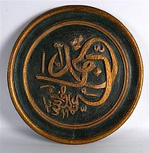 A TURKISH POLYCHROMED LACUERED WOODEN PLATE with central gilt calligraphy.