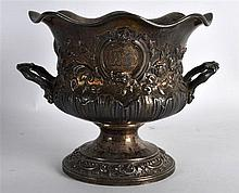 A GEORGE III TWIN HANDLED EMBOSSED SILVER URN decorated in relief with scro