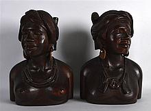 A PAIR OF AFRICAN CARVED HARDWOOD BUSTS. 10.5ins high.