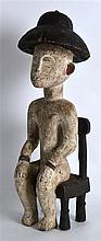 AN UNUSUAL CARVED AFRICAN COLONIAL POLYCHROMED WOOD FIGURE OF A SEATED MALE