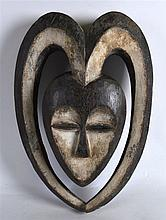 AN UNUSUAL CARVED AFRICAN TRIBAL MASK of stylish form. 1ft 2.5ins long.